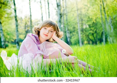Attractive girl with dandelion in perfect green grass