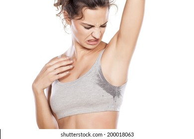 attractive girl is disgusted by her sweaty armpits