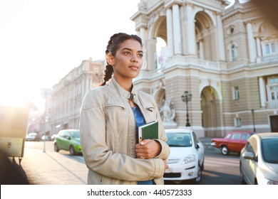 Attractive girl dressed in blue t-shirt and grey jacket  hold the book and catching the car at the street background.