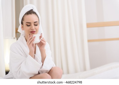 Attractive girl drinking beverage at spa