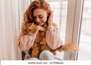 Attractive girl embracing her pet with smile. Indoor portrait of cute ginger woman playing with cat.