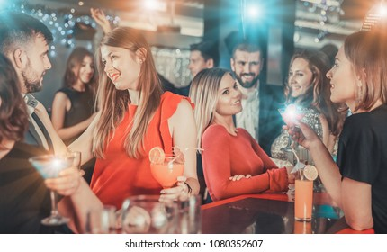 Attractive girl flirting with handsome man on a cocktail party in bar