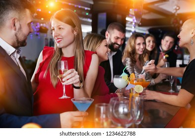 Attractive girl flirting with handsome man on a cocktail party at bar
