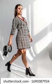 Attractive girl in a gray checkered dress on a white background
