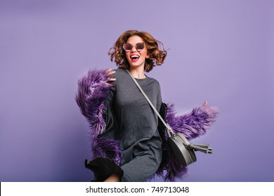 Attractive girl in gray dress and black sunglasses dancing in studio on purple background. Indoor portrait of charming young woman in fur coat having fun during photoshoot.