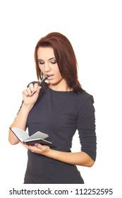 Attractive girl in a gray dress holding a pen and notebook and something in it reads. Isolated on white background