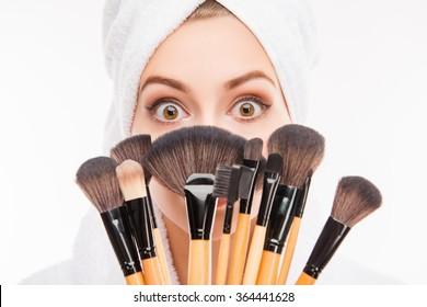 Attractive girl hiding behind makeup brushes