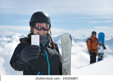 Attractive girl holding blank lift pass and ski smiling with snowboarder and mountain range in background. Concept to illustrate ski admission fee