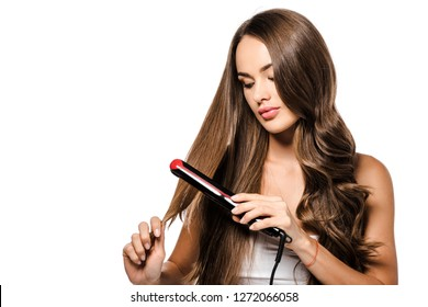 attractive girl holding hair and using straightener isolated on white