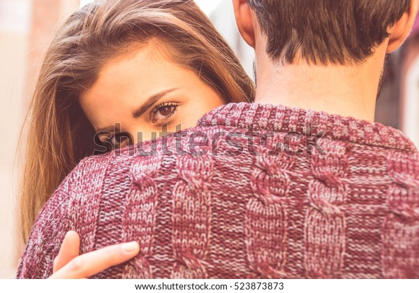 Attractive girl hugging her boyfriend and looking at the camera. Concept about love, people and lifestyle.