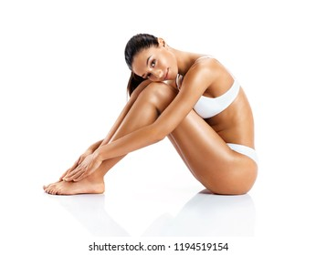 Attractive girl hugging her legs. Photo of young girl sitting on white background. Beauty and body care concept