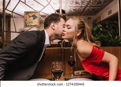 attractive girl kissing cheek of man in restaurant on valentines day