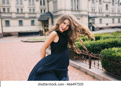 Attractive girl with long curly hair is walking on steer on old building background. Her black long dress and hair flying from wind and moving. She is smiling to camera.