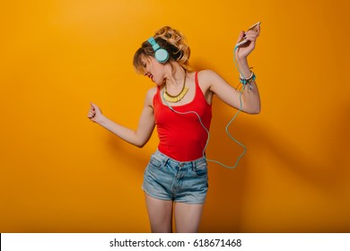 Attractive  girl with long curly hair in tail has fun on orange background in studio. She wears red T-shir, shorts and listening to energy music with blue headphones.