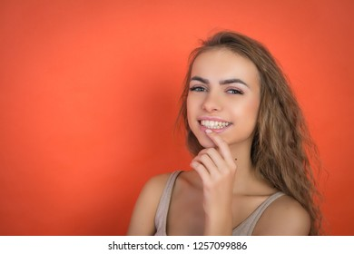 attractive girl looking at the camera on a red background