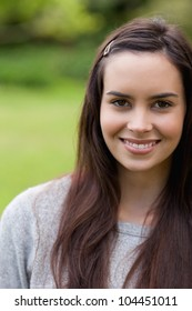 Attractive girl looking straight at the camera while standing in a park and smiling