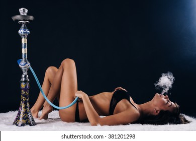 Attractive girl lying on the floor and smoking hookah