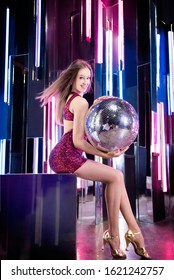 Attractive girl with mirror disco ball in night music club