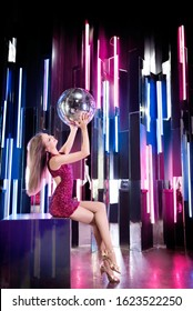 Attractive girl with mirror disco ball in night music club. Success