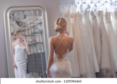 Attractive girl at the mirror in a wedding shop