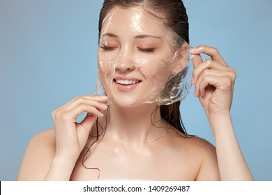attractive girl with naked shouldes and wet hair taking off facial mask with eyes closed, copy space, pretty female purifying face