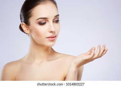 Attractive girl with nude make up posing at grey studio background, beauty photo concept, perfect skin, holding product.