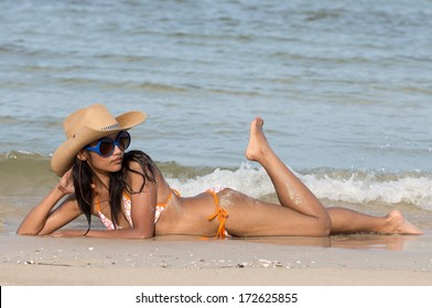 Attractive girl on seashore. Young woman with a cowboy hat lying on a sea beach. Sexy woman in bikini at the sea. Sensuality woman in bikini lying on the sand by the sea. Seductive girl in swimwear.