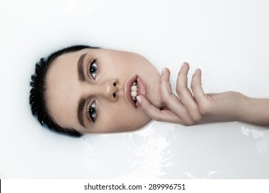 Attractive girl with open eyes takes a milk bath, touching her face. Perfect skin, nude makeup, romantic atmosphere, beauty cosmetic salon and spa treatment for woman's skin.