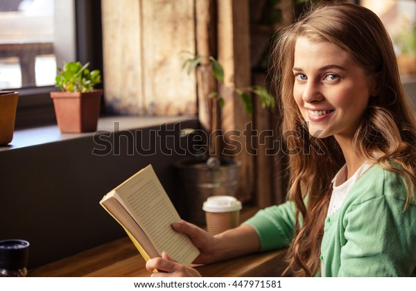 Attractive girl posing with book at coffee shop