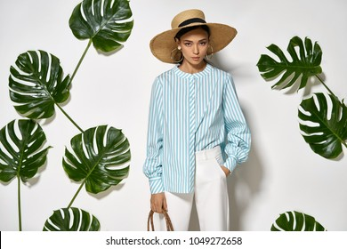 Attractive girl is posing in a studio on a background of a white wall with big green leaves. She wears a striped cyan shirt, white pants and a straw hat. Woman looks into a camera. Horizontal.