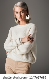 attractive girl posing in white knitted sweater and round earrings, isolated on grey
