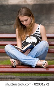 attractive girl is reading book in the city on the bench