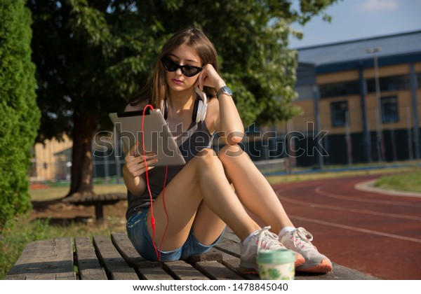Attractive girl reading e-book on a digital tablet on a bench in the park on a sunny summer day in the sunset. Girl wears sunglasses and headphones on the neck. Education concept