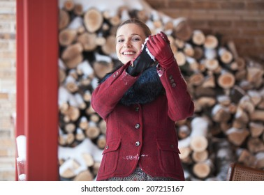 Attractive girl in red coat sculpts snowballs winter day
