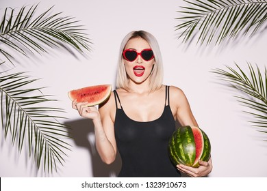 Attractive girl with red lips wearing black swimwear and sunglasses posing at white studio background with palms, holding watermelon, portrait, smile.
