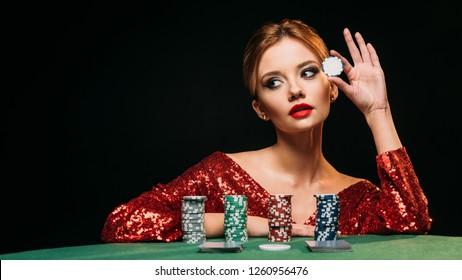 attractive girl in red shiny dress leaning on table, holding poker chip and looking away isolated on black