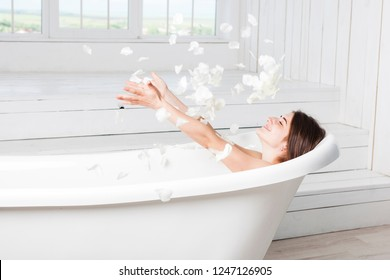 Attractive girl relaxing in bath on light background