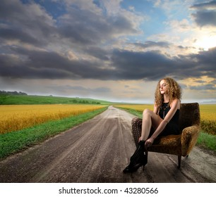 attractive girl seated in armchair in the countryside