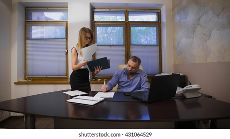 Attractive girl secretary brings documents to sign. Her boss respectable, gray-haired man, sitting in a private office in the director's chair.resolution.