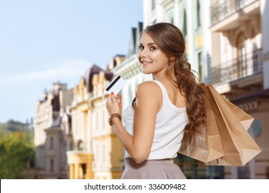 Attractive girl with shopping bags and credit card in the city