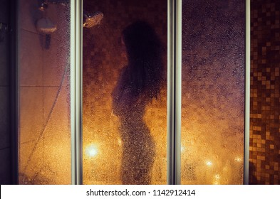 Attractive girl in a shower. Sensual darkness. A hot silhouette behind a wet curtain.