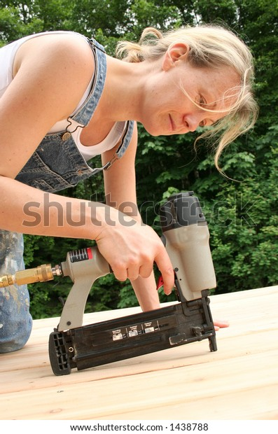 An attractive girl shows off her handywoman skills by nailing on new cedar decking.