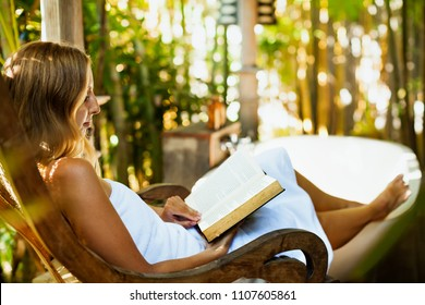 Attractive girl sit at rocking chair drinking morning coffee, reading romance in paper book. Relaxing woman fill bath tub in Boho style outside bathroom in luxury villa on summer tropical vacation.