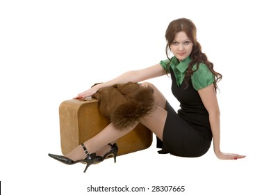 The attractive girl sits with an old suitcase