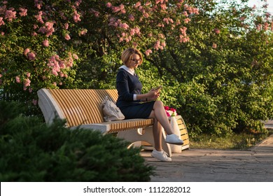 Attractive girl is sitting on park bench. She checks incoming e-mail messages on her phone. Backpack is next to her. Business lady is always in touch.