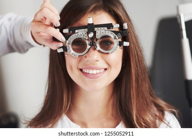Attractive girl smiling while wear phoropter that get tune by doctor.