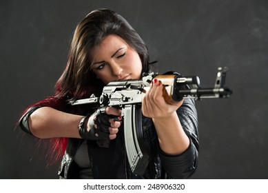 Attractive girl standing in the attitude of aiming and looking through the sight automatic rifle.