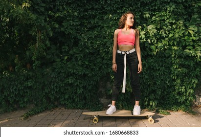 Attractive girl in stylish street clothes stands on a longboard on the background of the wall with ivy, looking away with a serious face. Fashionable street lady rides down the street on a longboard