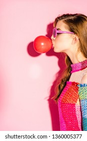 attractive girl in sunglasses blowing red bubble gum on pink