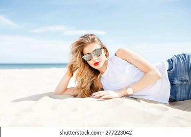 Attraktives Mädchen in Sonnenbrillen, die sich auf dem Meer Strand an einem sonnigen Tag auf dem Hintergrund des Meeres und des klaren Himmels.